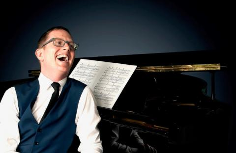 Man in waistcoat with black tie seated t piano laughing