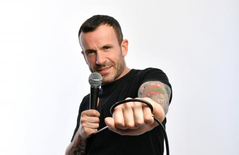 Gary in black t-shirt with microphone in right hand and left hand stretched out towards the camera.