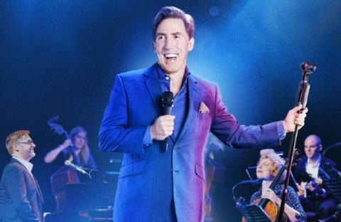 Rob in a blue suit smiling at audience with microphone in right hand